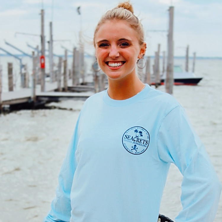 Young blonde female wearing blue long sleeved seacrets shirt